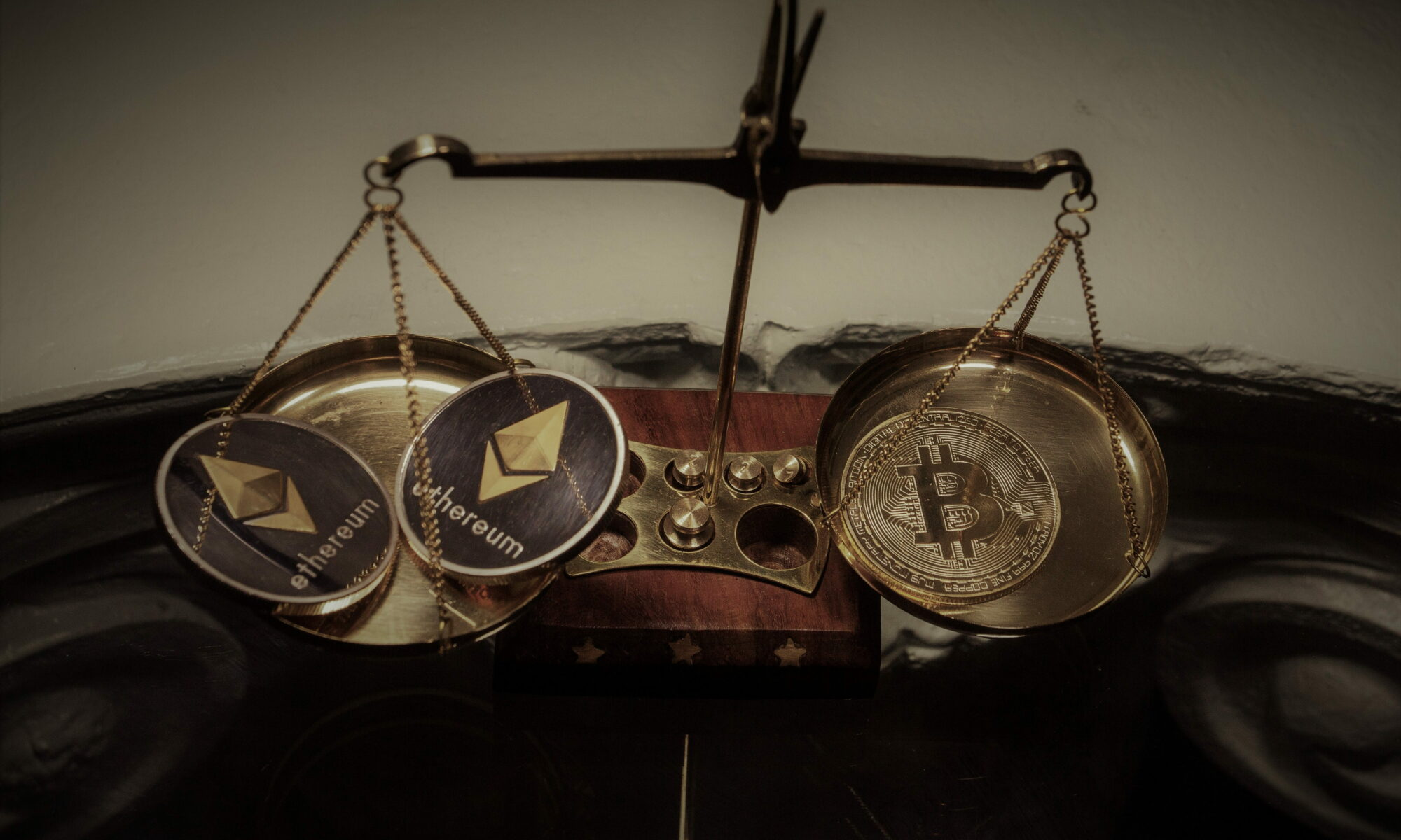 bitcoin and ethereum are placed on a balance to be differentiating with two ethereum coins and one bitcoin.